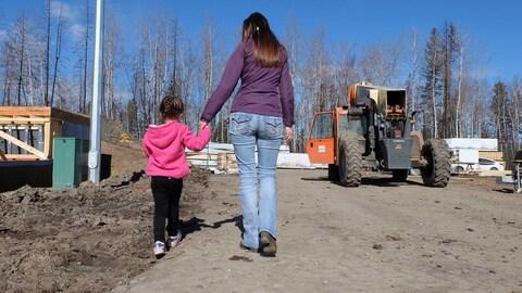 Photo de la mère et de la fille, de dos, marchant vers la construction de leur nouvelle demeure.