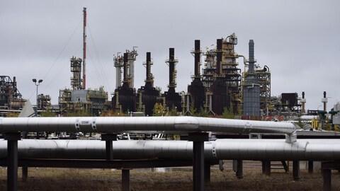 Des tuyaux gris devant des installations pétrolières.
