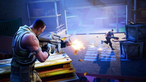 Une capture d'écran du jeu vidéo « Fortnite » montrant un personnage en train de tirer au fusil d'assaut sur un autre personnage qui tente de se cacher derrière des caisses en bois dans un hangar.