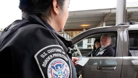 Un agent des douanes américaines en discussion avec deux personnes dans une voiture.