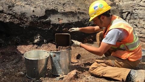 Un homme dépose de la terre dans une chaudière en métal.