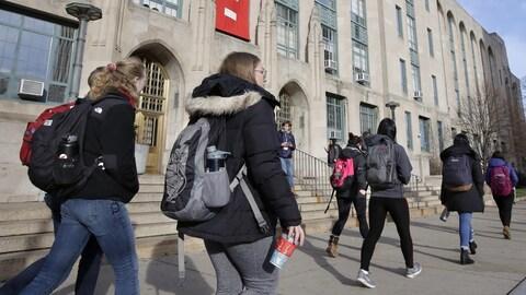 Des étudiants portant des sacs à dos marchent sur un campus universitaire.