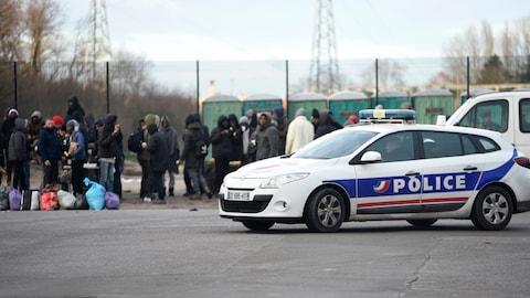 Une voiture de police est garé devant une file de migrants rassemblés à Calais dans le nord de la France