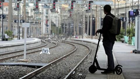 Un jeune avec sa trottinette sur le quai d'une gare.