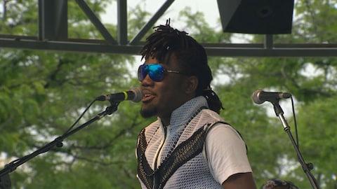 Photo d'un homme noir devant un micro portant des lunettes soleil