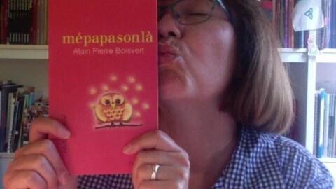 Une femme embrasse un livre rouge intitulé «Mépapasonlà», de l'écrivain Alain Pierre Boisvert.