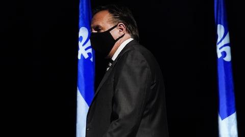 Le premier ministre François Legault, portant un masque, à son arrivée pour la conférence de presse.