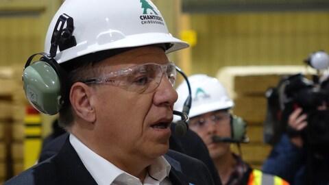 François Legault portant un casque et des lunettes de protection ainsi qu'un casque d'écoute, dans une usine.