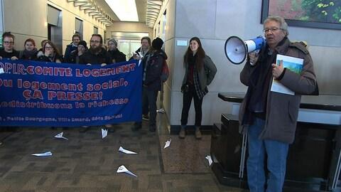 Un homme portant un manteau parle dans un mégaphone devant des manifestants tenant une banderole dans le hall à l'entrée d'un immeuble.