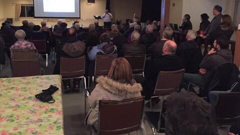 Quelques dizaines de personnes écoutent un animateur dans un grande salle.