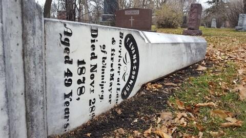 La stèle de la  pierre tombale de Frank Evans Cornish, le premier maire de Winnipeg, est allongée sur le sol et des feuilles d'arbres dans un cimetière