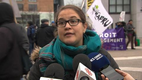 Émilie Joly est photographiée devant les micros de différents médias; derrière elle, des manifestants tiennent des pancartes réclamant des logements sociaux.