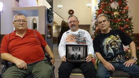 De gauche à droite : les frères Bob Preston, Don Preston et Richard Preston, trois anciens élèves des pensionnats autochtones de Terre-Neuve-et-Labrador. Ils sont assis. Don Preston tient dans ses mains un cadre avec une photo des trois frères lorsqu'ils étaient plus jeunes.