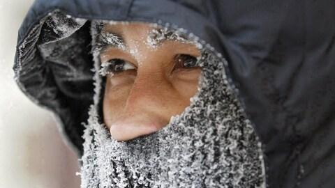 La face d'un homme couverte d'un capuchon et d'un foulard gelé.