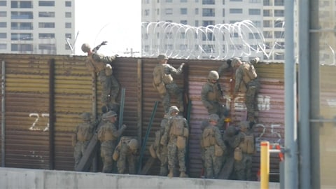 Une dizaine de militaires solidifient un mur en métal monté de fil barbelé à la frontière entre le Mexique et les États-Unis.