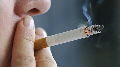 Une femme fume une cigarette.