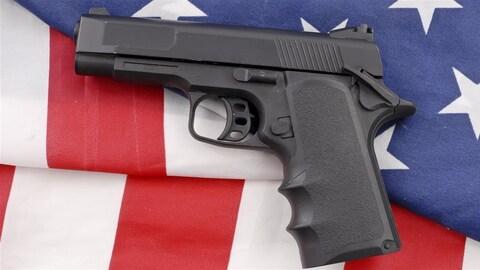 Une arme à feu est posée sur un drapeau américain.