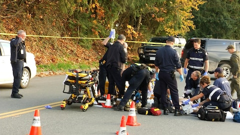 Une dizaine d'ambulanciers s'affairent à porter des soins à un blessé au beau milieu de la rue.