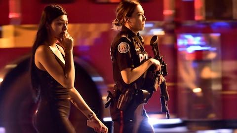 Une policière escorte une civile à l'écart des lieux d'une fusillade à Toronto le dimanche 22 juillet 2018.