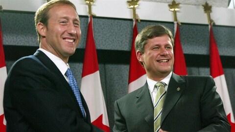 Peter MacKay et Stephen Harper, tout sourire, se serrent la main après une conférence de presse à Ottawa.