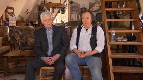 Gaétan Bégin et Pierre Bolduc, assis dans une pièce d'une maison ancienne, avec un escalier-échelle à droite sur l'image.