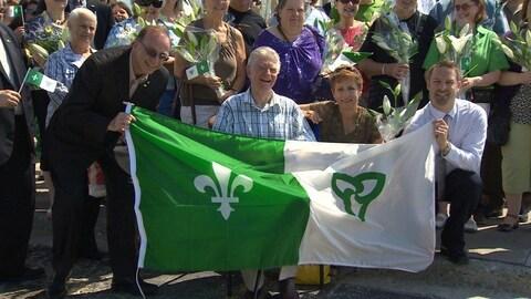 Gaétan Gervais, derrière un drapeau  franco-ontarien, entouré de dizaine de personnes.