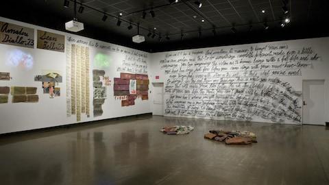 Grande salle avec de grosses écritures sur les murs, des fragments de papiers. Au sol, quelques vieux vêtements regroupés en deux tas.