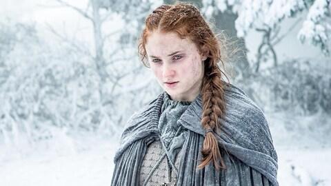Sophie Turner seule dans une forêt enneigée, dans la série  Game of Thrones .
