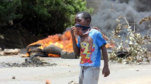 Un garçon se couvre le visage alors qu'il marche dans les rues de Kanyama, un bidonville de la capitale gambienne, qui a été le théâtre de manifestations, samedi.