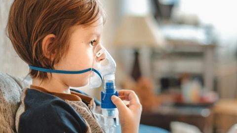 Un jeune garçon porte un masque respiratoire.