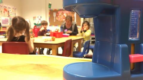 Une éducatrice à la petite enfance partage un repas avec des enfants.
