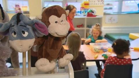 Des jouets sont à l'avant-plan de la photo qui montre aussi une éducatrice assise à une table avec des enfants.