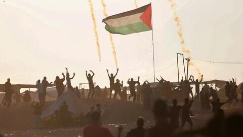 Des Palestiniens lèvent les bras au ciel pendant que des gaz lacrymogènes tombent. Un drapeau palestinien flotte au milieu de la foule.