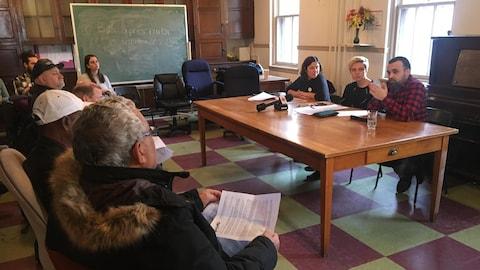 Des représentants d'organismes de défense des locataires assis autour d'une table parlent aux médias.