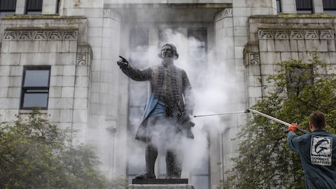 La Statue de George Vancouver est nettoyée aprèès avoir été vandalisée avec de la peinture à l'extérieur de la Mairie de Vancouver, le 11 juin 2020.