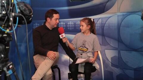 Gérald Fillion et une jeune visiteuse simulent une entrevue pendant les portes ouvertes de Radio-Canada.