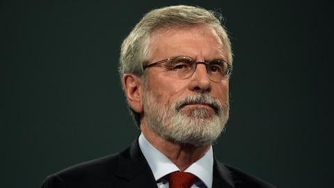 Gerry Adams, portant un complet, devant un écran gris.