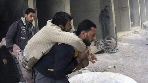 Un homme est porté par un autre après avoir été sorti des décombres. Derrière, un troisième lui tient la jambe.
