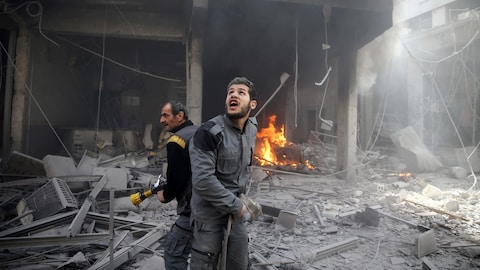 Un homme avec une hache regarde le ciel, alors qu'un autre tient une lance d'incendie, parmi des décombres.