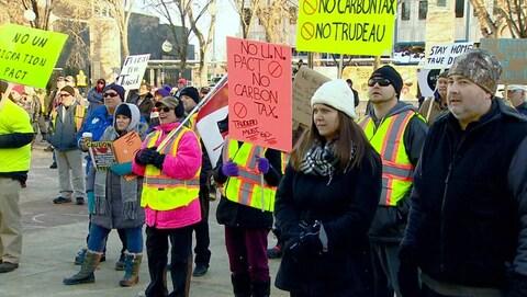 des manifestants se tiennent dehors. Ils ont des vestes jaune fluorescent et des pancartes colorées.
