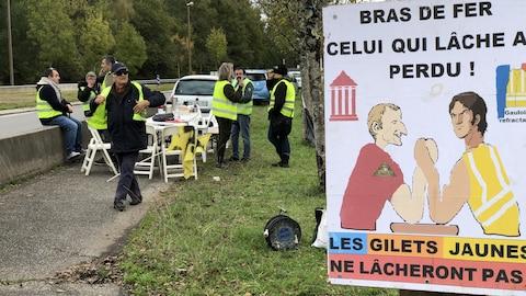 Une pancarte arbore une caricature qui dépeint le président Macron et un gilet jaune en séance de tir au poignet. « Celui qui lâche a perdu. Les gilets jaunes ne lâcheront pas. ». En arrière-plan, des manifestants réunis à côté d'une route.
