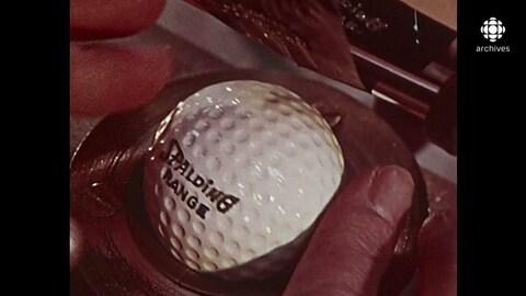Gros plan sur une balle de golf pendant qu'on lui appose un logo.