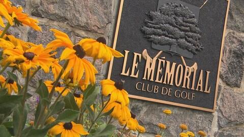 Affiche extérieur du Mémorial avec des fleurs devant