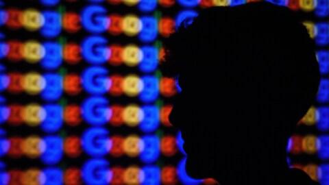 Un homme de profil se tient devant un mur où le mot Google est répété.