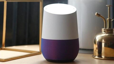 Une enceinte de forme cylindrique bicolore posée sur un comptoir