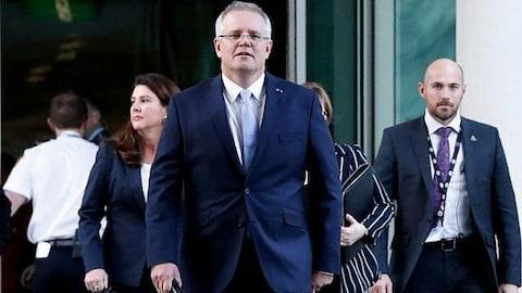 Le Premier ministre australien marche, accompagné de membres de son parti.