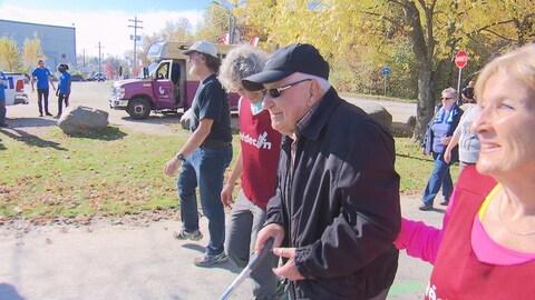 Il y a eu des participants de tous les âges à la Grande marche Pierre Lavoie de Sherbrooke. On aperçoit ici un candidat assez âgé qui marche avec le sourire et une canne dans les mains.