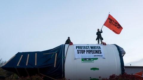 Deux femmes sur un tunnelier avec une affiche sur laquelle il est inscrit Protect Water, Stop Pipelines, ce qui signifie « Protégeons l'eau, arrêtons les pipelines ».