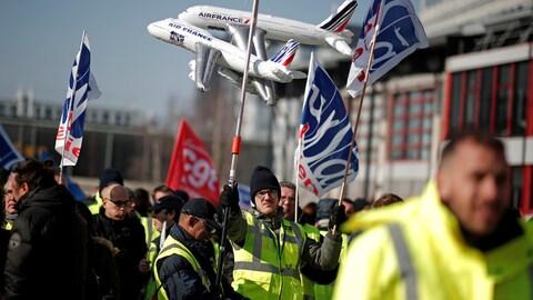 Des grévistes brandissent des drapeaux.