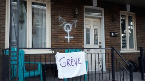 Un drap blanc sur un balcon sur lequel on peut lire ''grève''